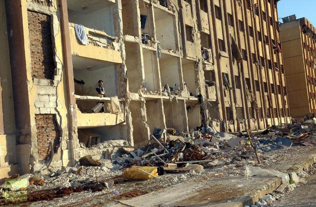 Seorang pria Suriah berdiri di puing-puing setelah sebuah ledakan di luar Universitas Allepo, antara asrama universitas dan fakultas arsitektur, pada 15 Januari 2013 (AFP Photo/STR)