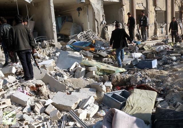 Sebuah foto berita yang dirilis oleh Syrian Arab News Agency (SANA) (Kantor Berita Arab Suriah—Red), menunjukkan orang-orang memeriksa tempat ledakan di luar Universitas Aleppo, antara asrama universitas dan fakultas arsitektur, pada 15 Januari 2013 (AFP Photo/Sana)