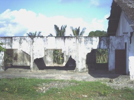 Rumah Raja NAK bagian utara (medio 2007, pascarenovasi bagian selatan). Tampak dari sisi kanan / arah barat; reruntuhan ketiga kamar tidur dengan dinding-dinding tak utuh; sisa-sisa lantai bersemen; di sebelah kanan terlihat Rumah Raja NAK bagian selatan yang telah direnovasi