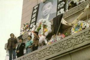 "18 April (1989—Red): Para mahasiswa memajang tinggi-tinggi spanduk yang menyerukan ""Pencerahan Kebebasan & Demokrasi"" di Monumen Martir,  Lapangan Tiananmen, dihiasi potret besar Hu Yaobang, dikelilingi karangan bunga yang didedikasikan kepadanya oleh para warga dari berbagai perguruan tinggi."