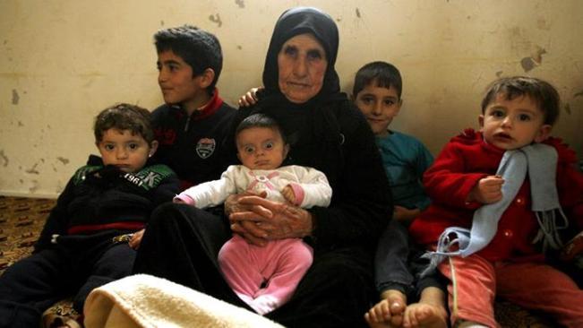 Hallum Al-Amin, seorang pengungsi Suriah, duduk dengan anggota keluarganya di sebuah rumah di desa Qalawayeh, dekat kota Lebanon selatan Tirus, pada tanggal 12 Januari 2014. (AFP Photo / Mahmoud Zayyat)