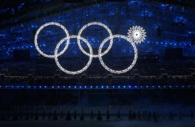 Para peserta berbaris sebagai salah satu dari Cincin Olimpiade yang gagal untuk tuntas berbinar saat upacara pembukaan Olimpiade Musim Dingin Sochi 2014, 7 Februari 2014. (Reuters / Phil Noble)