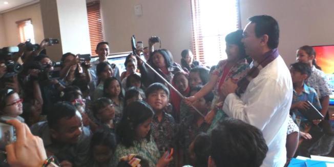 KOMPAS.COM/KURNIA SARI AZIZA Pelaksana Tugas (Plt) Gubernur DKI Jakarta Basuki Tjahaja Purnama (Ahok) menggendong seorang siswa yang berkunjung ke ruang kerjanya di Balaikota, kemudian berfoto
