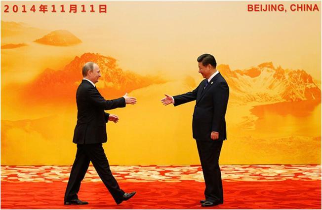 Presiden Rusia Vladimir Putin (Kiri) berjabat tangan dengan mitra kerjanya dari Tiongkok Xi Jinping selama Kerjasama Ekonomi Asia Pasifik (APEC), di Convention Center International, Danau Yanqi, distrik Huairou Beijing, 11 November 2014 (Reuters / Kim Kyung -Hoon)